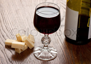 Glass with wine and cheese on a table