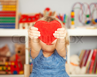 Happy child with small handmade paper red heart in class