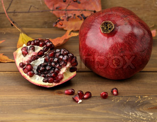 Ripe Pomegranate With Red Seeds On Wooden