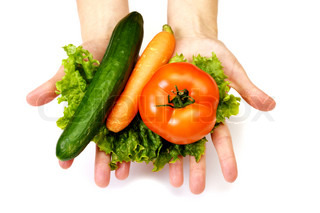 a variety of vegetables in their hands - carrot, cucumber, tomato on lettuce leaves