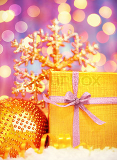 Golden gift box with baubles decorations, Christmas tree ornament for winter holidays, present with purple abstract bokeh shiny glowing blur lights background