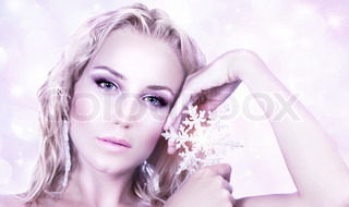 Beautiful woman in Christmas winter style, holding shining snowflake star, glamor female face with bright makeup, sexy girl portrait over abstract pink glowing bokeh holiday background