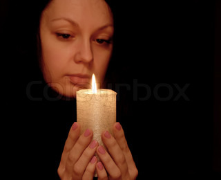 The woman with burning candle Selective focus on a candle