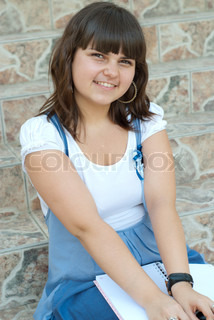 Smiling schoolgirl is sitting on stairs with notebooks