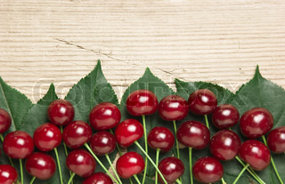 Berry Cherry with leaves on a wooden background