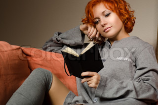 Red woman sitting on sofa reading small black notebook