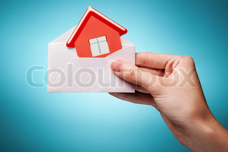 woman's hand holding an envelope with a sign of the house against blue background