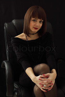 Girl on a chair against a black background