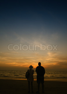 Couple of woman and man staying near sea and looking at sunset