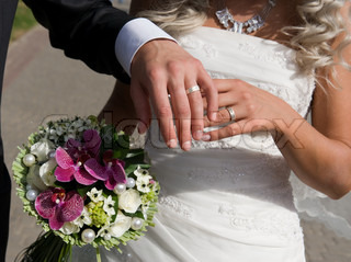 Portrait of two pairs of beautiful hands of bride and groom on the background of fabulous bouquet of flowers