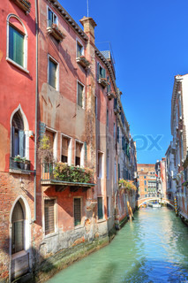 Vertical oriented image of small narrow canal among ancient houses under blue sky in Venice, Italy