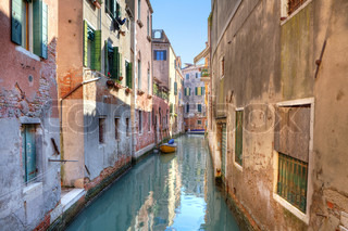 Small canal among old red brick houses in Venice, Italy