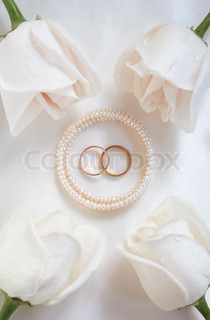Wedding rings and white roses can use as wedding background