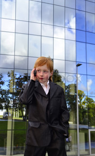 Smart boy talking by phone in front of an office building