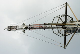 A metal frame telecommunication tower with transmission dish standing