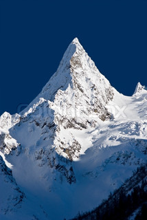 Snedækkede bjergtop en bjergryg og videregive tæt op imod lyst mørkeblå himmel i forgrunden snedækkede nåletræ caucasus Rusland