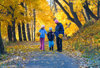 Happy family mother with small children walking in golden maple autumn park