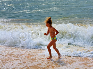Small girl play on beach with