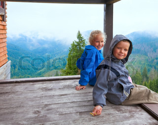 Small boy and girl on wooden cottage porch on mountain hill top and cloudy morning view behind