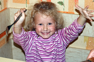 mischievous little girl in kitchen ready and glad to eat