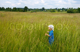 crying small boy in tallgrass on summer meadow