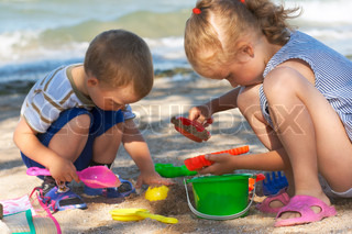 Small girl and boy play with sand near sea