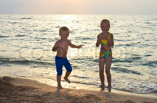 Small girl and boy play and dance near evening sea