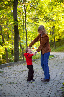 Happy family mother with small boy funny dance in golden autumn city park
