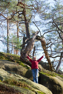 Happy woman on large stone in autumn forest