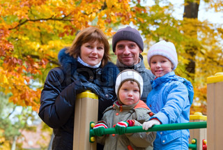 Young family parents with small children in golden autumn city park