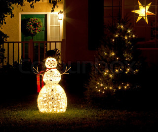 Christmas decorations snowman and Christmas tree with lights on green grass