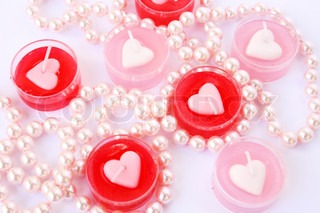 Heart shape red and pink candles with necklaceisolated on grey background