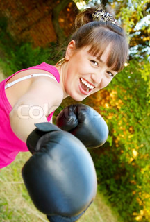 Merry girl in boxing-gloves on nature