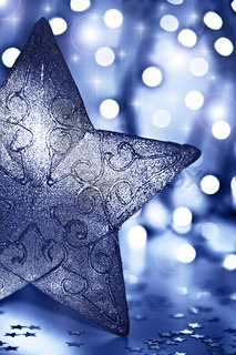 Star decoration, Christmas tree ornament, beautiful blue silver bauble over abstract blur bokeh lights background, decorating home at winter holidays, new year eve