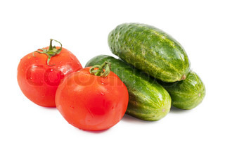 Fresh washed vegetables cucumbers and tomatoes over white background