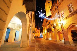 Alba old town central street with illuminations and Christmas Tree against San Lorenzo Cathedral on the background in Italy