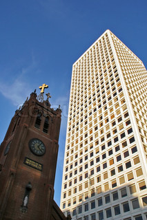 Vertical oriented image of old church against of modern office building under blue sky in San Francisco, USA