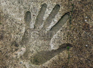 Human handprint in old weathered concrete floor