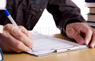 Man sitting and writing something with pen
