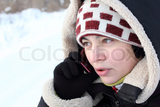 beautiful girl talking by mobile phone, in winter