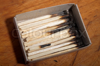 Box with burnt matches on a wooden table