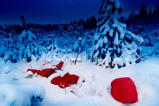 Santa lying in the snow with his presents sack near him