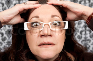 This woman has a crazy look on her face like she is shocked or astounded while holding her hands on her head