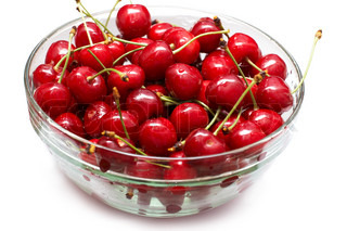 Red-ripe cherry in glass bowl on white background