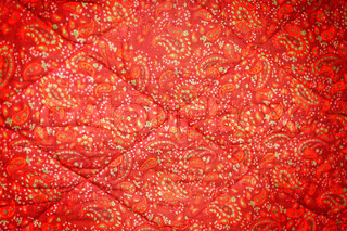 Red quilt with abstract pattern