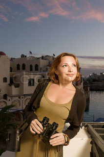 Tourist woman with binoculars in the evening at seaside