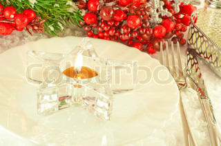Christmas table layout, candlestick in the form of a star with a branch of berries