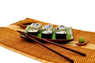Sushi rolls soya sauce wassabi and wooden chopsticks