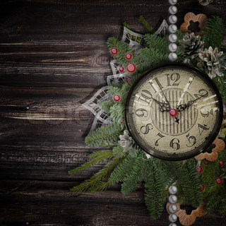 Antique clock face with pearls, lace and firtree on the wooden background