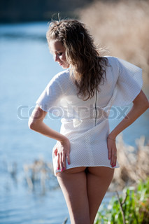 Portrait of sexy young woman in a mini dress posing against the backdrop of water somewhere in the nature